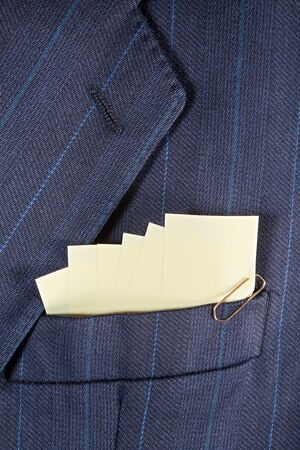 breast pocket: Yellow sticky note reminders in a breast pocket of a formal business suit
