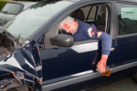 drinking and driving: Drunken driver hanging out of his crashed car Stock Photo