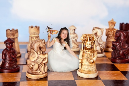 alice: Girl in alice in wonderland dress shrunken to miniature size of a chess piece