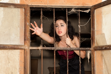 old bar: Desperate woman behind bars asking for help Stock Photo