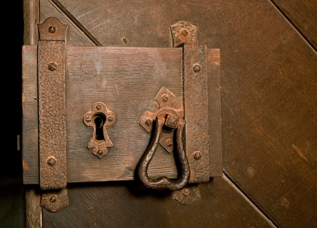 Antique rusty lock on a medieval wooden door photo