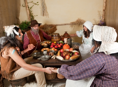 Reenactment scene of the first Thanksgiving Dinner in Plymouth in 1621 with a Pilgrim family and a Wampanoag Indian photo