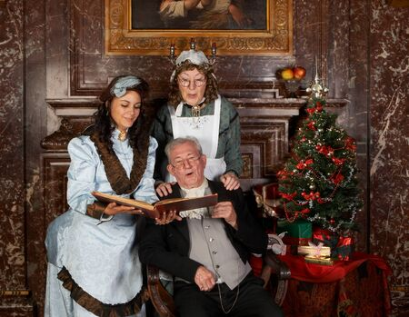 Vintage christmas scene of a victorian family singing christmas carols.Shot in the antique castle