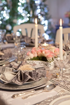candle lights: Christmas tree and fancy dinner table with folded napkins