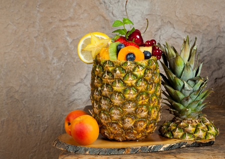 salad decoration: Pineapple filled with colorful assorted fruit salad Stock Photo