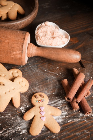 Rolling pin and homemade gingerbread men biscuits on a wooden board with flour photo