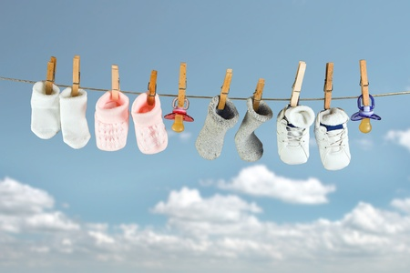 clothes pegs: Baby socks and shoes hanging on a clothesline in the sky Stock Photo