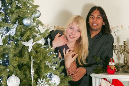 interracial couple: Young couple of different race posing at the christmas tree Stock Photo
