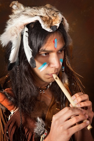 Portrait of an Indian in traditional costume wearing eagle feathers, coyote fur and beads photo