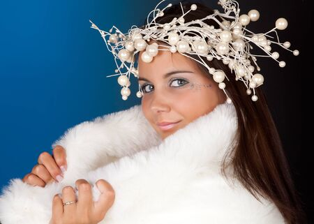 Winter girl wearing a white fur coat and pearl christmas wreath photo