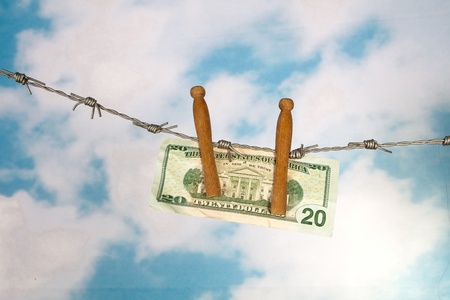 Barbed wire and clothes pegs holding a dollar note photo