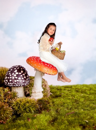 Cute little girl sitting on a toadstool in a fairytale photo