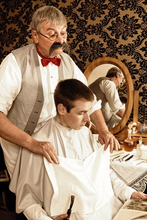 Victorian barber preparing the shave of a customer (the antique magazine is from 1910 = 101 years old). photo