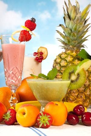 batidos de frutas: Grupo de mesa con frutas de verano y batidos de colores