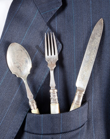 breast pocket: Antique silver spoon fork and knife in a breast pocket of a formal business suit Stock Photo