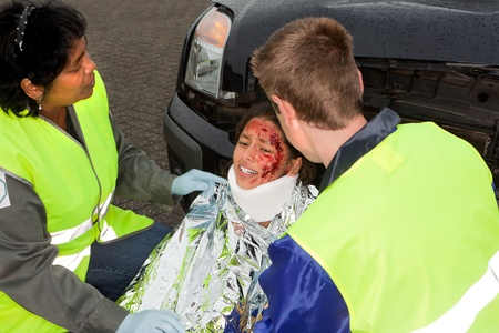 Paramedics helping a young injured victim of a car accident (note : the logo on the sleeve is replaced by a non existing logo) photo