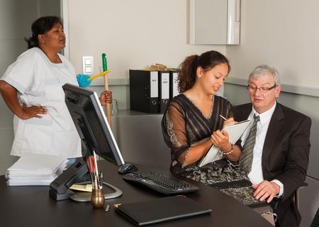 dictating: Mujer de la limpieza viendo una secretaria sentada en el regazo de su jefe