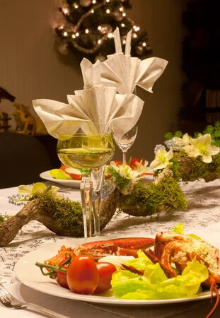 Festive dinner table with flower arrangement, lobster and white wine photo