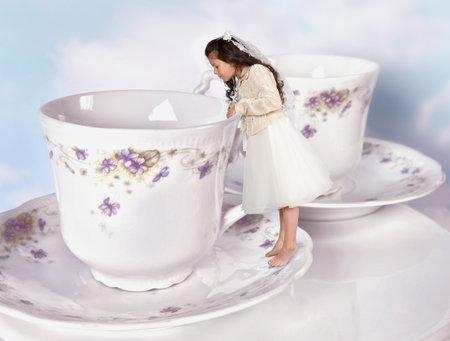 alice au pays des merveilles: Fille miniature dans Alice au pays des merveilles robe r�duit � la taille d'une tasse de th� Editeur