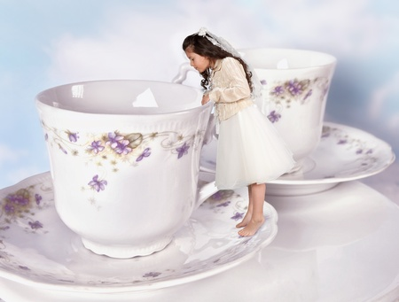 wonderland: Miniature girl in alice in wonderland dress shrunk to the size of a teacup