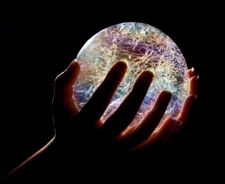 Handen die een gloeiende kleurrijke glazen of kristallen bol Stockfoto