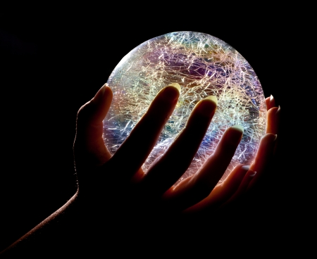 Hands holding a glowing colorfull glass or crystal ball