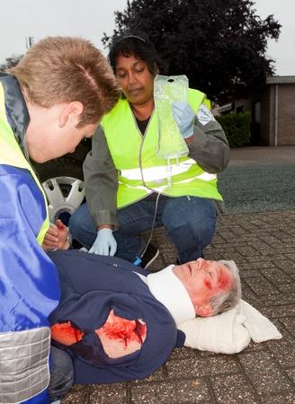 hemorragias: Herido tras accidente automovil�stico conseguir un cuello ortop�dico y un goteo intravenoso (manga las insignias fueron reemplazados por inexistentes logos) Foto de archivo