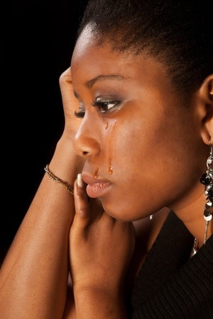Tears running of the face of a young african woman photo