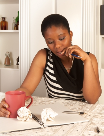 Pensive african woman writing a letter at home Stock Photo - 11423596