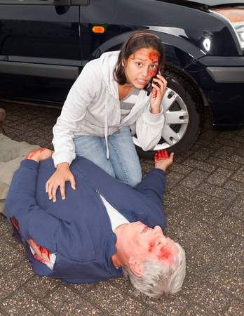 Injured woman calling for an ambulance after a car accident photo
