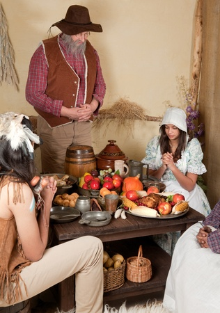 Reenactment scene of the first Thanksgiving Dinner in Plymouth in 1621 with a Pilgrim family and a Wampanoag Indian Stock Photo - 11762768