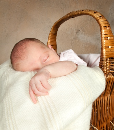 Wicker picnic basket with a little baby of 18 days old photo