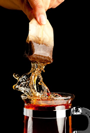 teabag: Fingers making a splash while removing a tea bag from hot tea Stock Photo