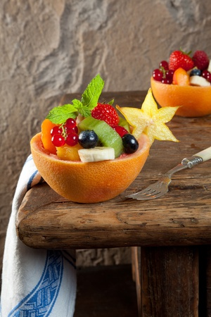 vintage table and colorful fruit salad in a grapefruit bowl photo