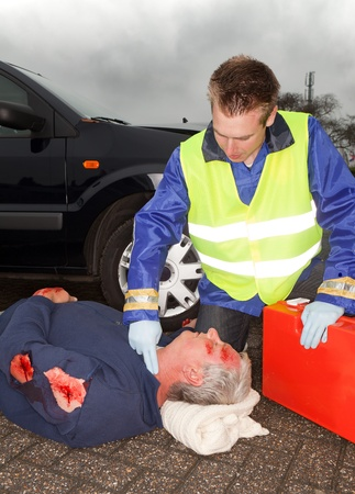 Wounded car crash victim being checked by a paramedic photo