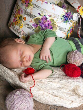 Newborn baby sleeping with colorful knitting wool photo