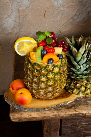 Pineapple filled with colorful assorted fruit salad photo
