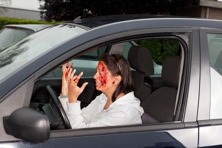hemorragias: Mujer joven, presa del pánico mirando sus manos manchadas de sangre después de un accidente de coche