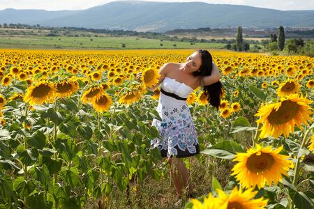 Pretty woman walking alone in a Bulgarian sunflower field photo