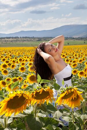 Relaxing pretty woman in a yellow bulgarian sunflower field Stock Photo - 11755573
