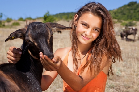 Young cattle girl feeding goats in the Bulgarian mountains photo