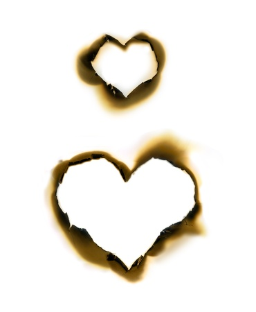 burned paper: Sheet of parchment with heart shape burnt holes Stock Photo