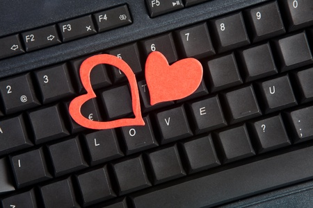 Red hearts on a computer keyboard on Valentines day photo