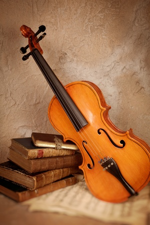 Old classical violin with antique books and grungy sheet music photo