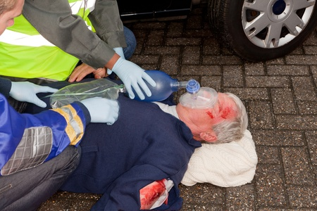 Wounded man after car crash being resuscitated with oxygen mask photo