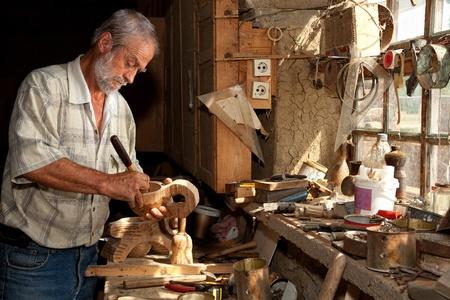 Houtbewerker carving hout in een vervallen schuur