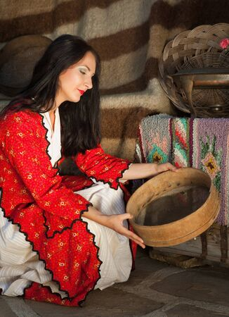 bulgarian ethnicity: Woman wearing a traditional bulgarian folklore costume holding a wheat sieve Stock Photo