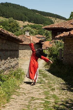 bulgarian ethnicity: Happy Bulgarian woman in traditional costume dancing in the streets of Jeravna