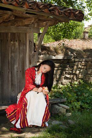 Bulgaarse vrouw in klederdracht het eten van een appel in het oude dorp van Jeravna Stockfoto
