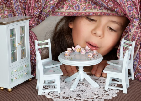 Little girl looking through a window into a dolls house like in alice in wonderland